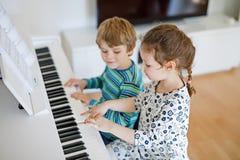 Dos niños muchacha y muchacho que juegan el piano en sala de estar o escuela de música fotografía de archivo