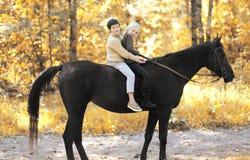 Dos niños muchacho y montar a caballo de la muchacha en caballo en otoño Imagen de archivo