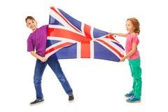 Dos niños, muchacho y muchacha agitando la bandera inglesa Fotografía de archivo