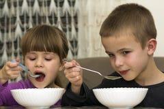 Dos niños muchacho y muchacha que comen la sopa con la cuchara de los wi de una placa Imagen de archivo libre de regalías