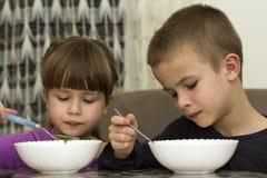 Dos niños muchacho y muchacha que comen la sopa con la cuchara de los wi de una placa Fotografía de archivo libre de regalías