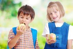 Dos niños muy lindos que comen las frutas al aire libre Foto de archivo libre de regalías