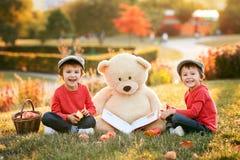 Dos niños pequeños adorables con su amigo del oso de peluche en el parque imagen de archivo