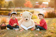 Dos niños pequeños adorables con su amigo del oso de peluche en el parque fotos de archivo libres de regalías