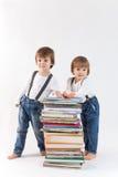 Dos niños pequeños con una pila de libros Imagen de archivo libre de regalías