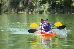 Dos niños pequeños diversos kayaking abajo de un río hermoso Foto de archivo