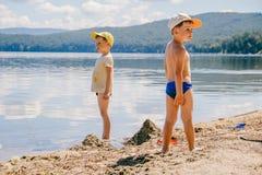 Dos niños pequeños en casquillos están en el lago en el verano imagenes de archivo