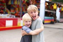 Dos niños pequeños felices que abrazan y que sonríen en el americano de la pequeña ciudad fotografía de archivo