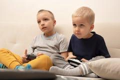 Dos niños pequeños juegan en la consola del juego foto de archivo
