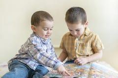 Dos niños pequeños lindos están estudiando un libro Dos niños pequeños en camisas con un libro Concepto de educación Imagen de archivo libre de regalías