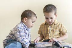 Dos niños pequeños lindos están estudiando un libro Dos niños pequeños en camisas con un libro Concepto de educación Foto de archivo