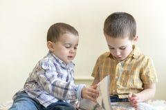 Dos niños pequeños lindos están estudiando un libro Dos niños pequeños en camisas con un libro Concepto de educación Imagen de archivo