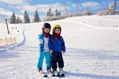 Dos niños pequeños lindos, hermanos, esquiando en un día soleado Fotografía de archivo
