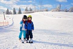 Dos niños pequeños lindos, hermanos, esquiando en un día soleado Fotografía de archivo libre de regalías