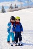 Dos niños pequeños lindos, hermanos, esquiando en un día soleado Foto de archivo