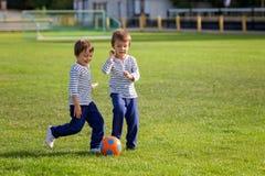 Dos niños pequeños lindos, jugando a fútbol Foto de archivo