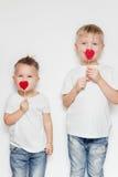 Dos niños pequeños que se colocan con el corazón forman en los palillos de madera contra el fondo blanco Foto de archivo libre de regalías