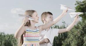 Dos niños positivos que juegan con los aviones de papel simples Imagen de archivo