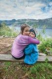 Dos niños que abrazan cada uno encima Foto de archivo