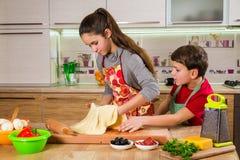 Dos niños que amasan la hoja fina de la pasta, haciendo la pizza Imagen de archivo