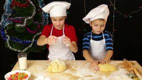 Dos niños que amasan la pasta para las galletas de la Navidad junta metrajes