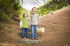 Dos niños que caminan abajo de los pasos de madera con la cesta afuera. Fotografía de archivo