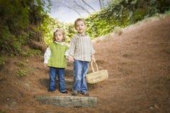 Dos niños que caminan abajo de los pasos de madera con la cesta afuera. Foto de archivo libre de regalías