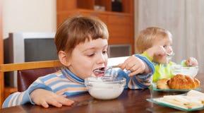 Dos niños que comen el desayuno de la lechería Fotografía de archivo