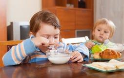 Dos niños que comen el desayuno de la lechería Fotografía de archivo libre de regalías