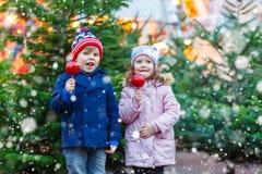 Dos niños que comen la manzana del azúcar en mercado de la Navidad Imágenes de archivo libres de regalías