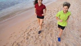 Dos niños que corren junto en los exersises de la mañana almacen de metraje de vídeo