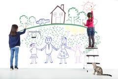 Dos niños que dibujan su sueño en la pared blanca Imagen de archivo