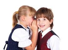 Dos niños que dicen secretos Imagen de archivo libre de regalías