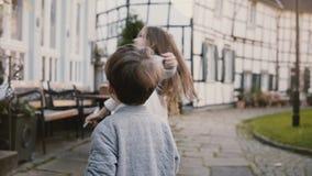 Dos niños que hacen las caras, bailando afuera Muchacha y muchacho caucásicos con el oso de peluche La media madera contiene el f almacen de video