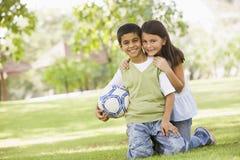 Dos niños que juegan al balompié en parque Imagen de archivo libre de regalías