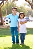 Dos niños que juegan al fútbol junto Imagen de archivo