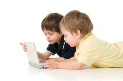 Dos niños que juegan con la computadora portátil Imágenes de archivo libres de regalías