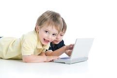 Dos niños que juegan con la computadora portátil Fotos de archivo libres de regalías