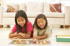 Dos niños que juegan el juego de mesa en el país imagen de archivo libre de regalías