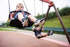 Dos niños que juegan en el oscilación Foto de archivo