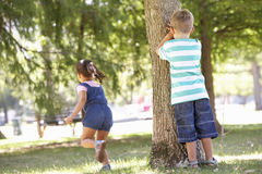 Dos niños que juegan escondite en parque Imagen de archivo libre de regalías