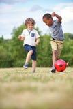 Dos niños que juegan a fútbol Imagen de archivo
