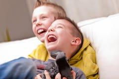 Dos niños que juegan a los videojuegos Imágenes de archivo libres de regalías