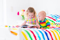 Dos niños que leen un libro en cama Foto de archivo libre de regalías