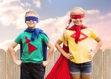 Dos niños que llevan al super héroe visten la situación con las manos en cadera Imagen de archivo