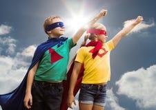 Dos niños que llevan al super héroe visten la situación contra fondo del cielo Imágenes de archivo libres de regalías