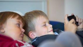 Dos niños que miran el vídeo en smartphone almacen de video