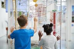 Dos niños que miran un objeto expuesto de la ciencia, visión trasera foto de archivo