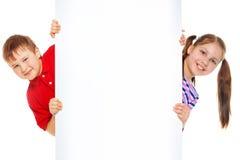 Muchacho y muchacha con el tablero de publicidad en blanco Foto de archivo libre de regalías