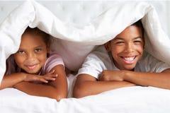 Dos niños que ocultan debajo del edredón en cama Fotos de archivo libres de regalías